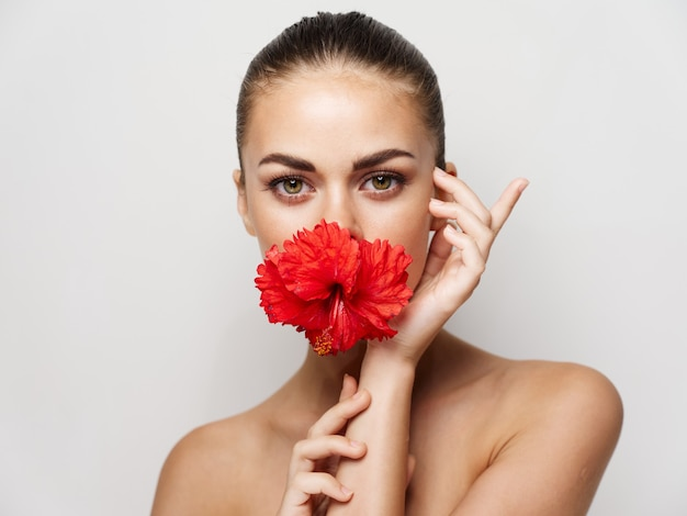 彼女の口の裸の肩のクローズアップに赤い花を持つきれいな女性