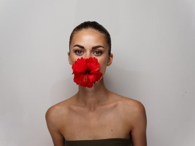 彼女の口の裸の肩の化粧品の明るい背景に赤い花を持つきれいな女性。高品質の写真 Premium写真