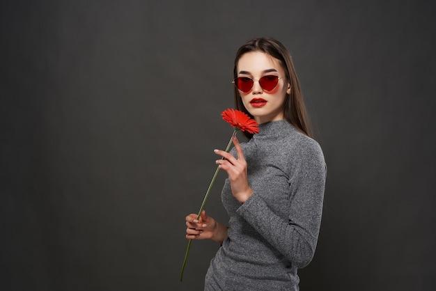 赤い花の唇を持つきれいな女性明るいメイクスタジオ