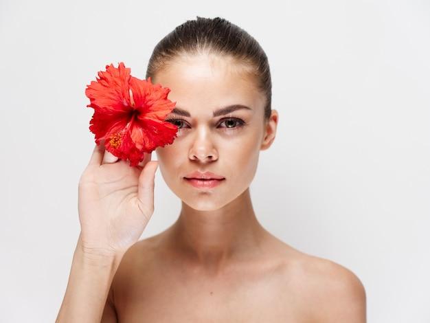 顔の裸の肩の近くに赤い花を持つきれいな女性