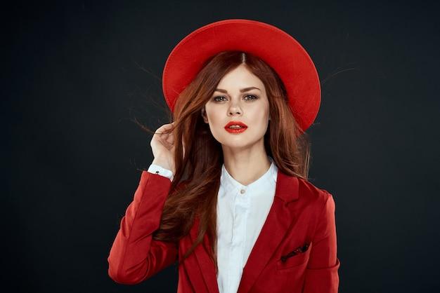 Красивая женщина с красными губами в шляпе на ее головной куртке элегантный стиль очарование темного изолированного пространства