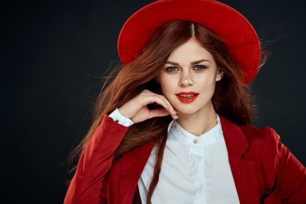 彼女の頭のジャケットに赤い唇の帽子を持つきれいな女性エレガントなスタイルの魅力ダーク