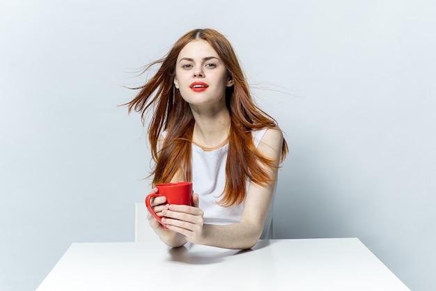 Красивая женщина с красными губами сидит за столом чашкой с напитком, расслабляясь в кафе