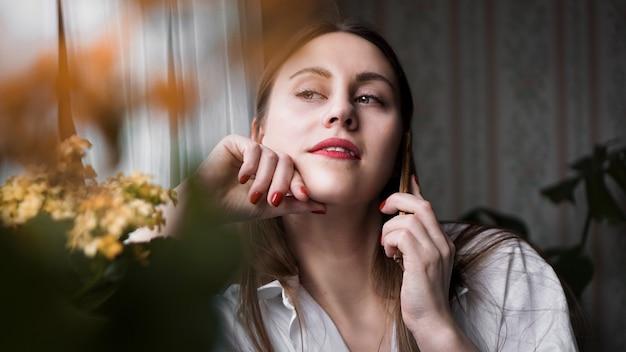 朝日光の下で自宅の窓の近くで電話で話している赤い唇を持つきれいな女性