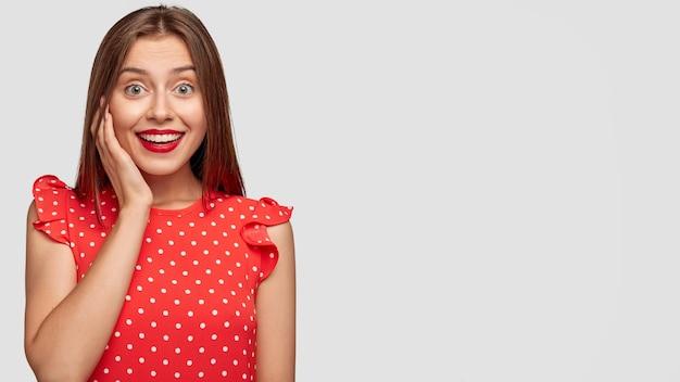 白い壁にポーズをとって赤い口紅を持つきれいな女性