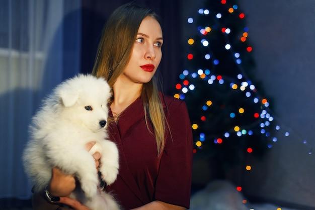 クリスマスの装飾でサモエドハスキー犬ときれいな女性