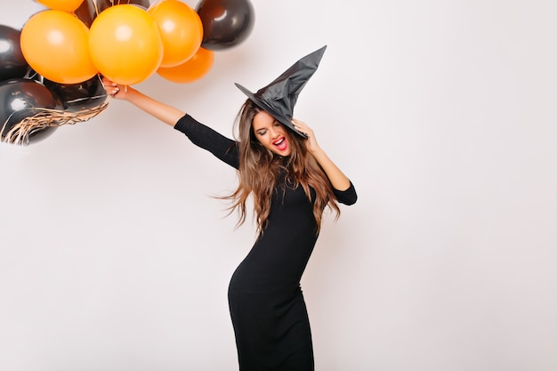 Pretty woman with shiny hair holding orange halloween balloons