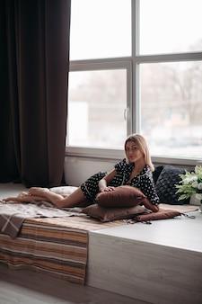 枕を持って笑顔の短いブロンドの髪のきれいな女性