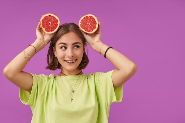 短いブルネットの髪のきれいな女性、紫色の壁の上のコピースペースで右を見て、彼女の頭の上にグレープフルーツを持っています。緑のtシャツ、歯列矯正器、ブレスレット、ネックレスを身に着けている