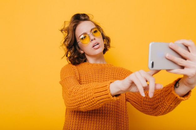 Bella donna con i capelli ricci corti che tiene smartphone e digitando un messaggio davanti al muro giallo