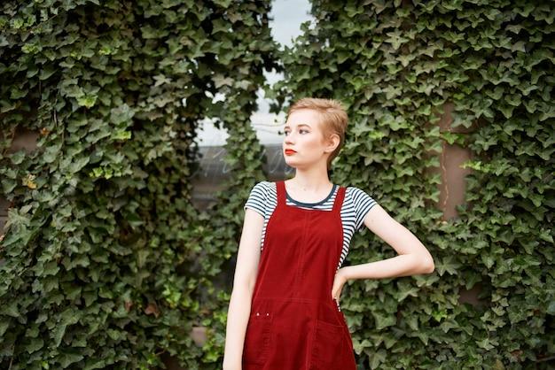 茂みの背景に屋外で短い髪のきれいな女性
