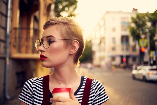 短い髪のメガネを屋外で一杯の飲み物を持つきれいな女性