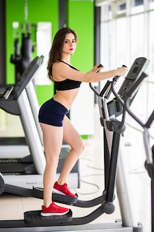 Pretty woman with slim fitness body works on elliptical trainer alone in sportclub