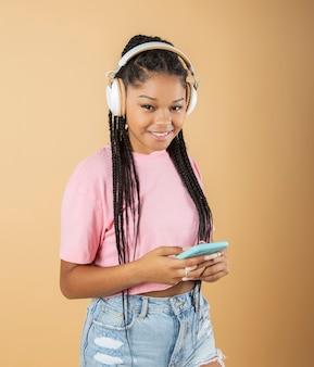 スマートフォンとヘッドフォンを持つきれいな女性は、ベージュの背景で、音楽を聴きます、