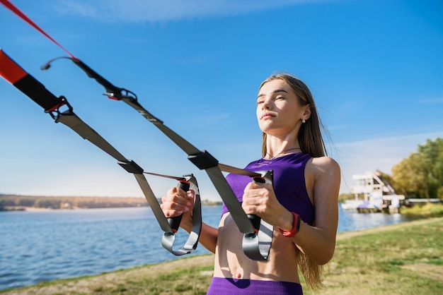 Pretty woman with sportwear doing crossfit push ups with trx fitness straps outdoors near the lake at daytime. healthy lifestyle