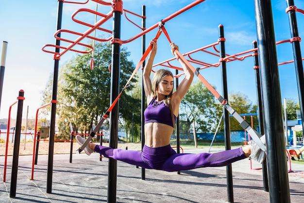 クロスフィット腕立て伏せをしているスポーツウェアのきれいな女性は、昼間、湖の近くの屋外でtrxフィットネスストラップを使用しています。健康的な生活様式。