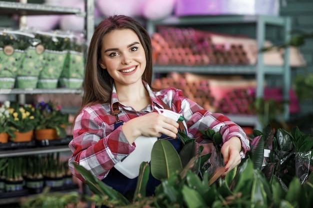 スプレーボトルスプレー植物を持つきれいな女性
