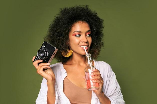 Красивая женщина со стильной прической позирует с камерой и пьет лимонад