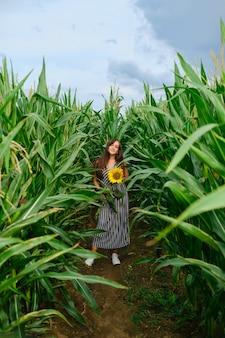 とうもろこし畑に立っている彼女の手にひまわりを持つきれいな女性
