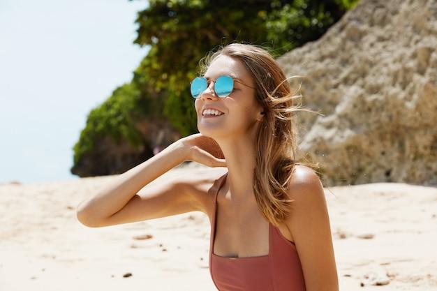 Красивая женщина в солнцезащитных очках и купальнике на пляже