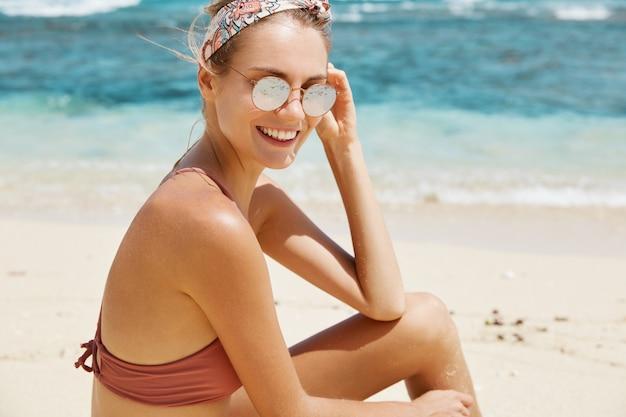 サングラスとビーチで水着のきれいな女性