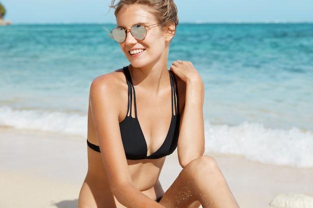Bella donna con occhiali da sole e costume da bagno sulla spiaggia