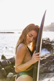 Pretty woman with surfboard on sea shore
