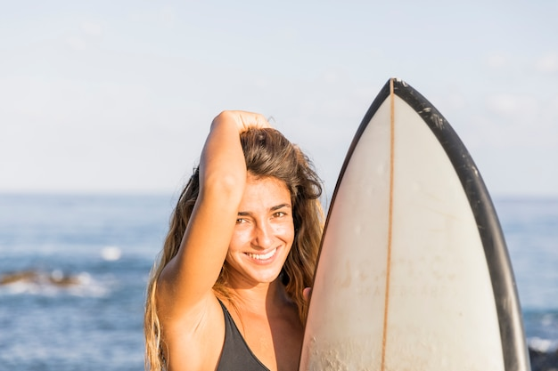 Pretty woman with surfboard touching hair