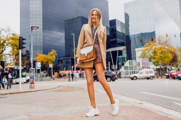 거리를 따라 걷는 놀라운 얼굴로 예쁜 여자. 베이지 색 코트와 운동화를 착용. 뉴욕. 완벽한 긴 다리. 우아한 표정.