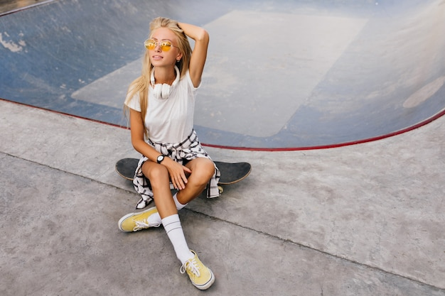 Pretty woman with tanned skin sitting on skateboard and playing with blonde hair.