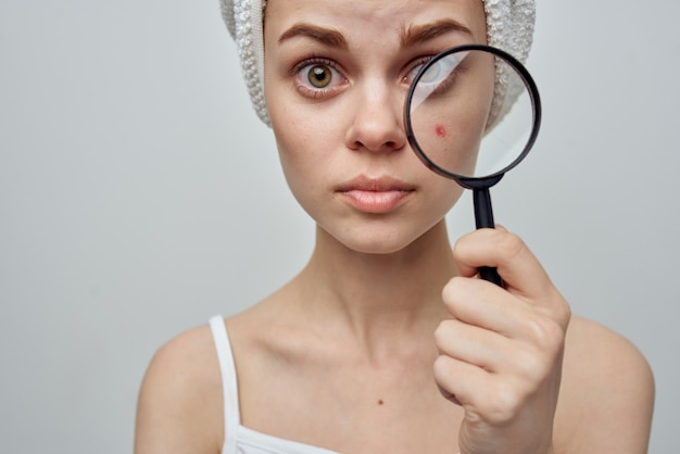 Pretty woman with a towel on her head holding a magnifying glass in her hands acne on her face