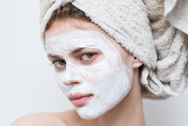 Красивая женщина с полотенцем на голове кремовая маска на лице крупным планом