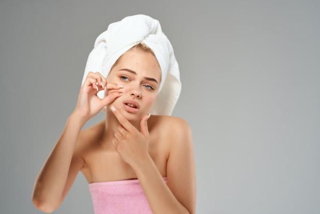 Красивая женщина с полотенцем на голове выдавливает прыщи на лице. фото высокого качества