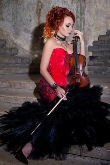 Красивая женщина со скрипкой. скрипачка и актриса. девушка в образе и сценическом платье, костюме в старой фактурной комнате держит или играет на скрипке. концепция музыкального плаката. место автора на фото