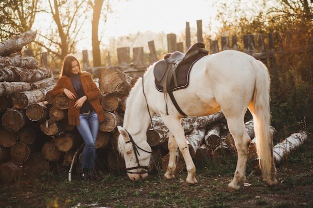 Красивая женщина с белым жеребцом в сельской местности.