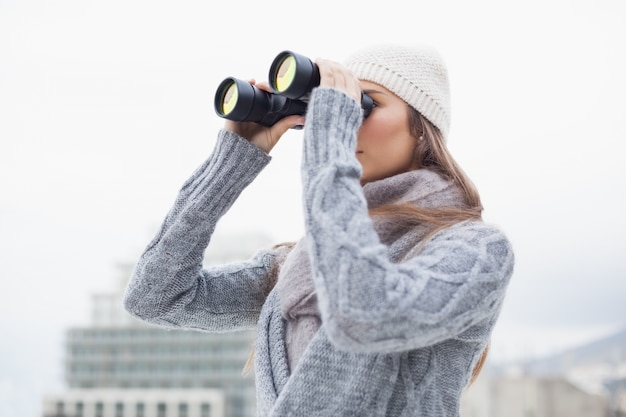 Pretty woman with winter clothes on looking through binoculars