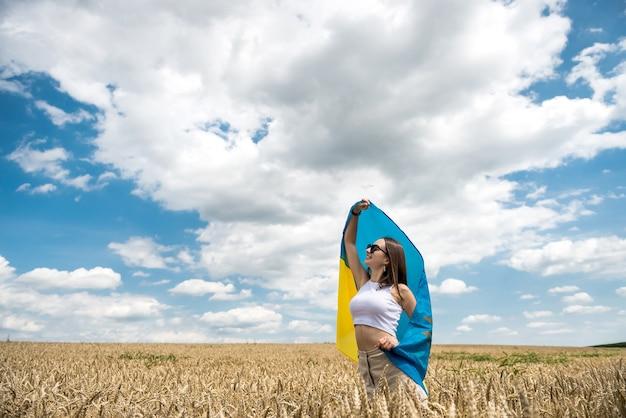 밀밭에 우크라이나의 노란색-파란색 국기와 예쁜 여자