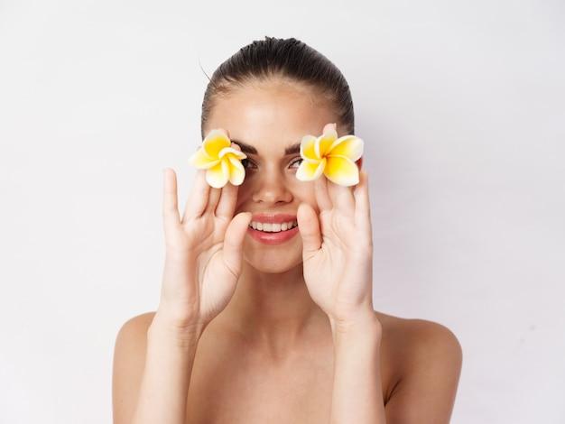 노란 꽃을 가진 예쁜 여자 벗은 어깨 미소 스튜디오