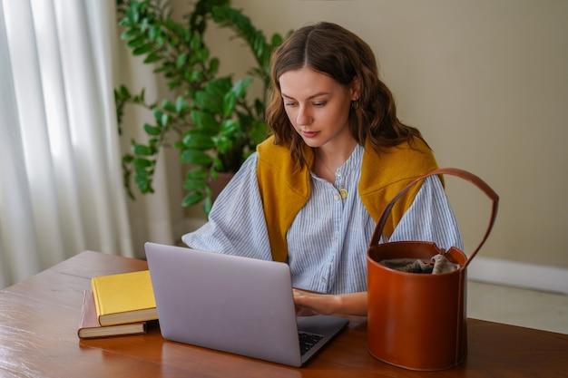 彼女のホームオフィスで働いているきれいな女性は、彼女のリビングルームで時間を楽しんで笑顔で終わります。