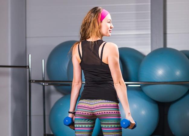 ジムでダンベルを使って運動するきれいな女性
