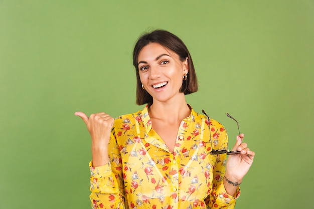 Pretty woman in yellow summer dress and sunglasses, green studio, excited cheerful joyful point finger left