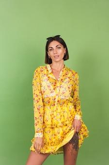 Pretty woman in yellow summer dress and sunglasses, green studio, happy positive cheerful joyful emotions