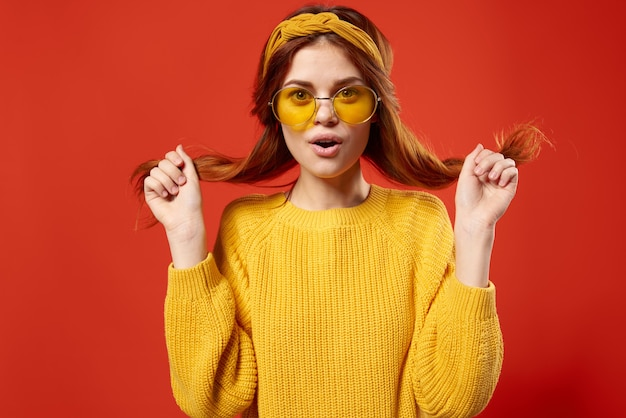 Pretty woman in yellow sweater holding hair emotions cropped view red.