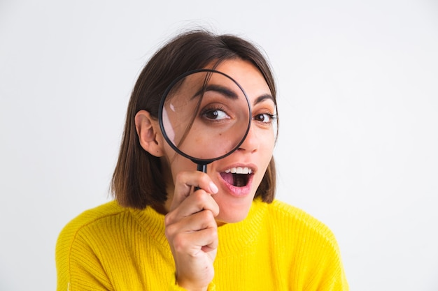 Pretty woman in yellow sweater on white  held magnifier happy positive playful