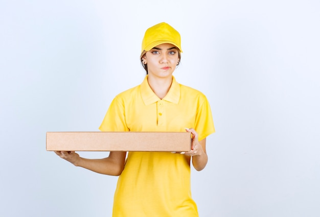 A pretty woman in yellow uniform holding a brown blank craft paper box .