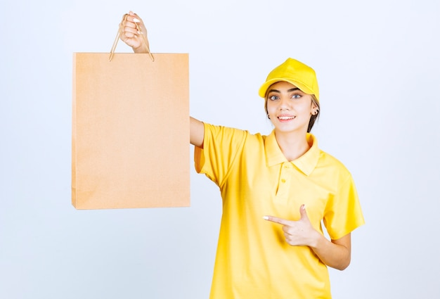A pretty woman in yellow uniform pointing at a brown blank craft paper bag .