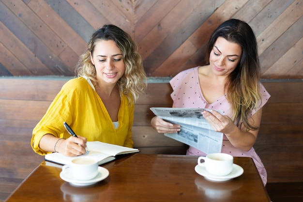 Pretty women drinking coffee and reading newspaper in cafe