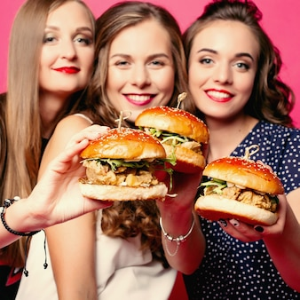 Pretty women friends with juicy hamburgers.