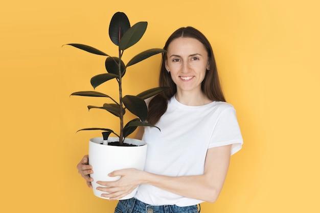 손에 평화 백합 냄비와 관엽 식물을 들고 웃 고 예쁜 여자