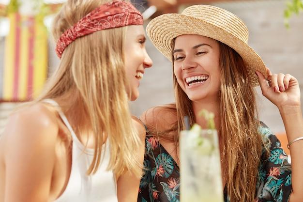 예쁜 여자들은 커피 숍에서 함께 재현하고 신선한 칵테일을 마신다. 편안한 사랑스러운 여성들은 여름 방학 동안 휴식을 취합니다.